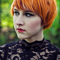 Portrait of a young female with short orange hair, dark make up and red lipstick, wearing a lace dress, looking away from the camera, with green forest background.