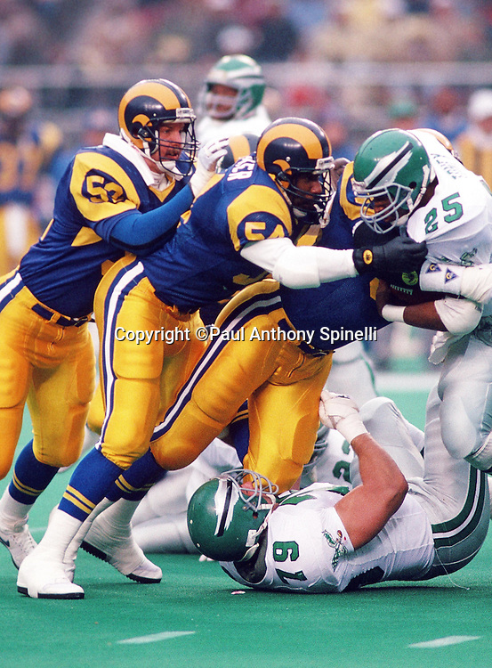 Philadelphia Eagles running back fullback Anthony Toney (25) gets gang tackled by Los Angeles Rams linebackers Larry Kelm (52) and Mike Wilcher (54) during the NFL NFC Wild Card playoff football game against the Los Angeles Rams on Dec. 31, 1989 in Philadelphia. The Rams won the game 21-7. (©Paul Anthony Spinelli)