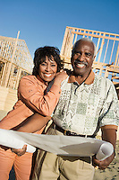 Middle-aged couple holding blueprint in front of house construction site portrait