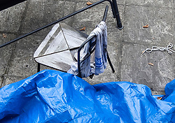 NOTE TO EDITORS : IMAGE TAKEN FROM A SUPERMARKET CAR PARK © Licensed to London News Pictures. 19/07/2019. London, UK. An NHS towel hangs on a partly burnt chair in the back garden of a house where it is reported that the body of a woman was found on fire in Chadwell Heath, East London. Fire fighters arrived at the house and then called in the police when they found the woman. Photo credit: Peter Macdiarmid/LNP