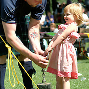 "August 18, 2007 -- BRUNSWICK, Maine.  Jeff Graham, of Windham, an amateur competitor at Saturday's Maine Highland Games at Thomas Point Beach in Brunswick, lifts a 56 pound ""half-stone"" with the help of his daughter, Marin, aged 2 and 1/2. Photo by Roger S. Duncan."