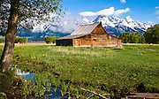 The early morning's soft light illuminates an old homestead in Jackson Hole Valley. The Tetons mountain range is in the background. Grand Tetons National Park, Wyoming.