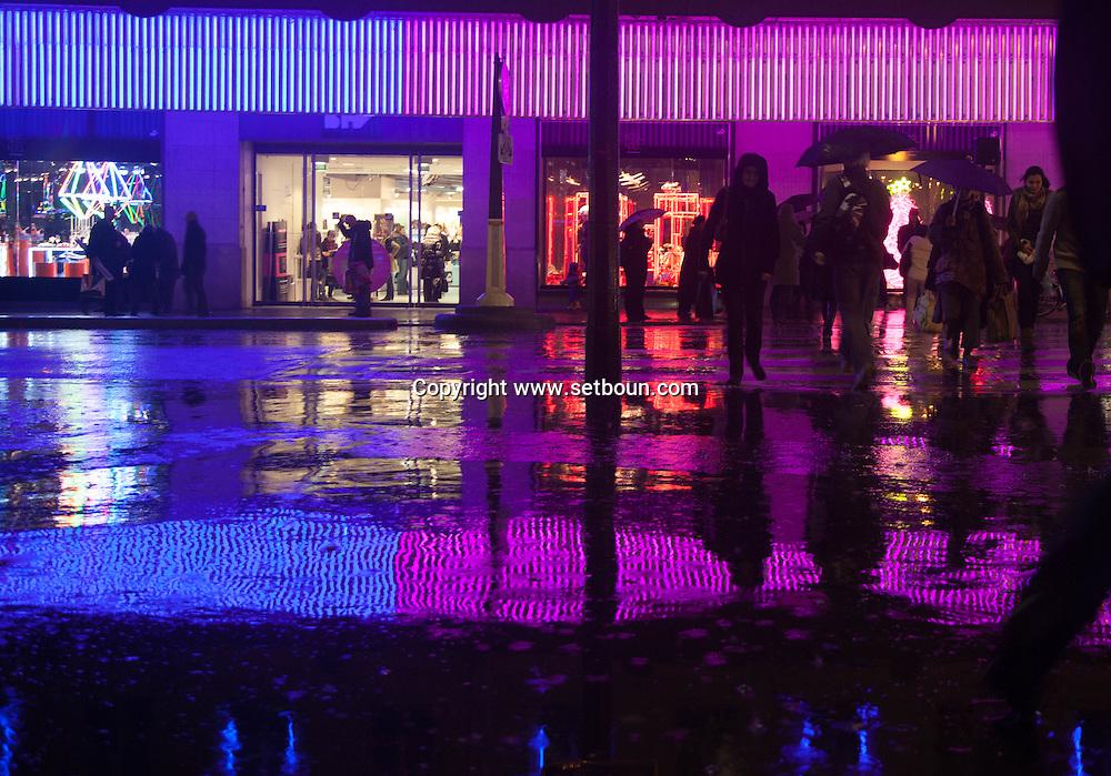 France. Paris. 4th district..  pedestrians shadows and reflection on Rivoli street under the rain at night