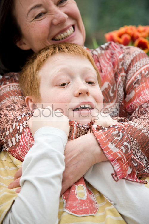Close up of a smiling woman hugging a boy