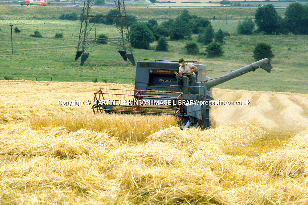Farmer wearing a dusk mask operating an open cab 1972 Ransomes combine harvester ......