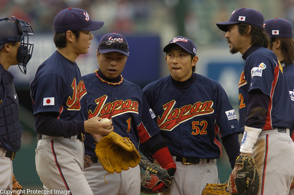 A conference on the mound as Team Japan's infield talk to starter Koji Uehara in the 3rd inning against Team USA in Round 2 action at Angel Stadium of Anaheim.