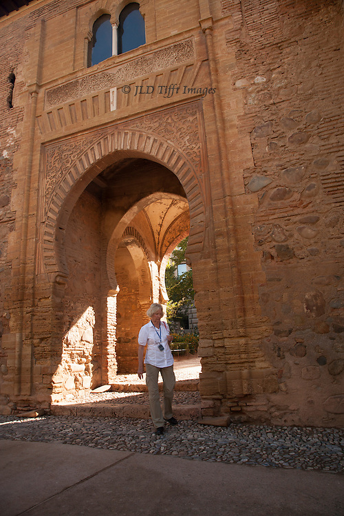 Blonde woman tourist steps through the Puerta del Vino in the Alhambra.
