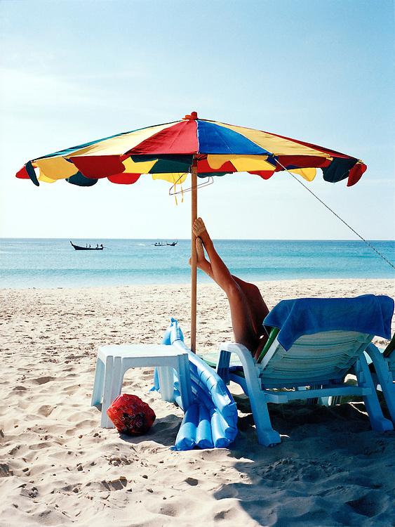 Tourist resting under beach umbrella on Karon Beach