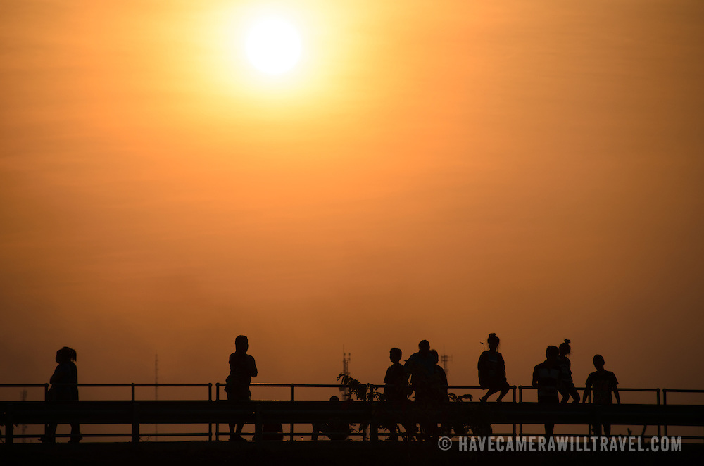 People enjoying the late afternoon on the banks of the Mekong are silhouetted against the setting sun with a hazy sky as they use the walkway along the river's edge in downtown Vientiane, Laos.