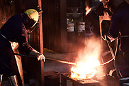 Pacific Steel Casting Company employee slags molten alloy