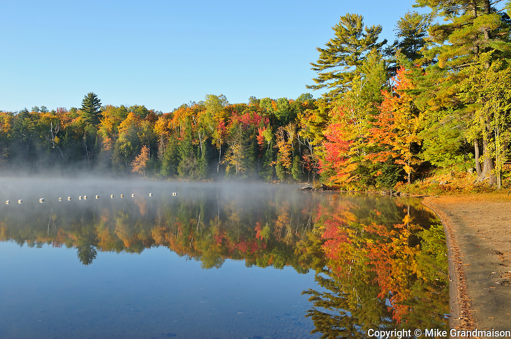 Sandy beach and  forest in autumn foliage reflected in Silent Lake<br /> Silent Lake Provincial Park<br /> Ontario<br /> Canada