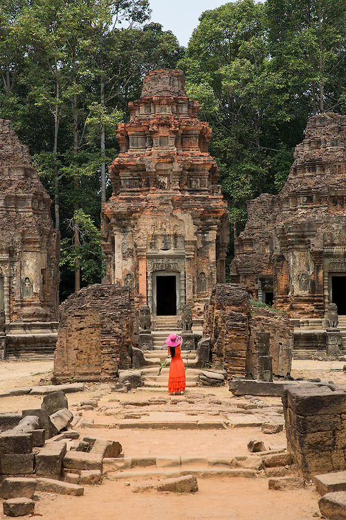 A woman in a red dress and bright pink hat stands in front of the central tower of the ancient Preah Ko temple, Roluos, Svay Chek District, Banteay Meanchey Province, Cambodia, South East Asia. <br /> The tower is made of brick and perches on a sandstone platform. This tower is dedicated to Jayavarman II, the founder of the Khmer empire.  (photo by Andrew Aitchison / In pictures via Getty Images)