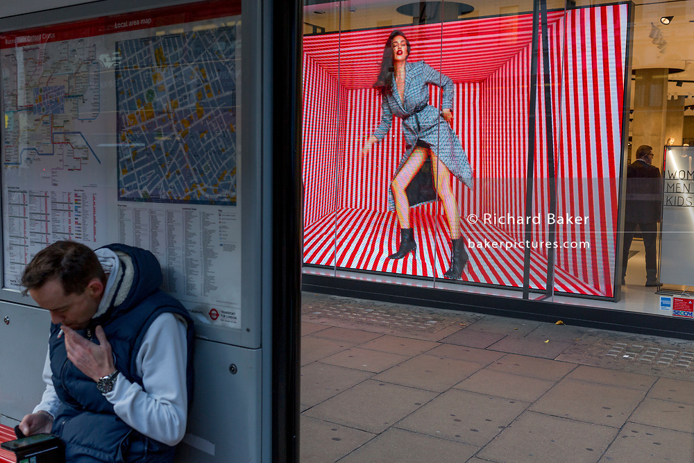 A bus traveller smokes in a bus shelter near a video loop for the London retailer 'Reserved', on Oxford Street, on 22nd November 2017, in London England.