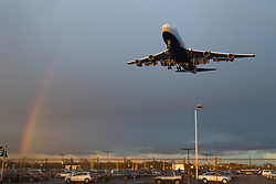 Heathrow Airport, London, March 28th 2016. The last rays of the sun create a rainbow as Storm Katie's last showers drift eastwards, and bathe an approaching British Airways Boeing 747 in golden light as it lands at London Heathrow.