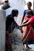 TAMIL NADU, MARCH 1994.A woman is restraining her daughter while the father is throwing cold water over her. Another woman is watching the scene while the young woman keeps weeping.