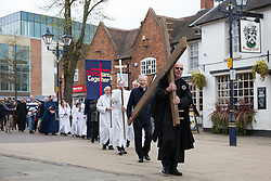© Licensed to London News Pictures. 14/4/2016. Solihull, West Midlands, UK.  Easter Walk of Witness taking place in Solihull. Pictured, the procession makes it's way to St Alphege Church. All the churches of Solihull coming together. Starting at St Augustine's Church around two hundred people walked behind a wooden cross into Mell Square for readings and prayers before continuing the walk to St Alphege Church.  Photo credit: Dave Warren/LNP