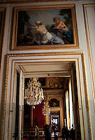 Paintings, chandeliers and golden door frames line a corridor in the Palace of Versailles.