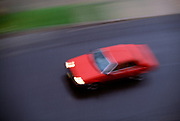 Red car blurring by on road below
