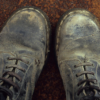Pair of well-worn black heavy-duty industrial working boots standing on rusty metal sheet