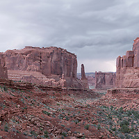 An approaching thunderstorm produces lightning flashes down the Park Avenue rock formations. Arches National Park, Moab, Utah.