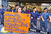 "09 JUNE 2013 - BANGKOK, THAILAND: A Thai Muslim woman who is a member of the White Masks, marches past Thai riot police during a protest against the government of Yingluck Shinawatra at Central World. The White Mask protesters wear the Guy Fawkes mask popularized by the movie ""V for Vendetta"" and the protest groups Anonymous and Occupy. Several hundred members of the White Mask movement gathered on the plaza in front of Central World, a large shopping complex at the Ratchaprasong Intersection in Bangkok, to protest against the government of Thai Prime Minister Yingluck Shinawatra. They say that her government is corrupt and is a ""puppet"" of ousted (and exiled) former PM Thaksin Shinawatra. Thaksin is Yingluck's brother. She was elected in 2011 when her brother endorsed her.     PHOTO BY JACK KURTZ"