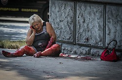A wounded woman sits on the street after a mortar attack by the Ukrainian army of the center of Donetsk, Ukraine, 14 August 2014. Reports state that ten local people where wounded and one killed after the mortar attack.