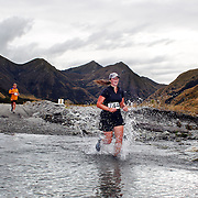 Runner Nadia McLean crosses  Moke Creek on the Ben Lomond High Country Station during the Pure South Shotover Moonlight Mountain Marathon and trail runs. Moke Lake, Queenstown, New Zealand. 4th February 2012. Photo Tim Clayton