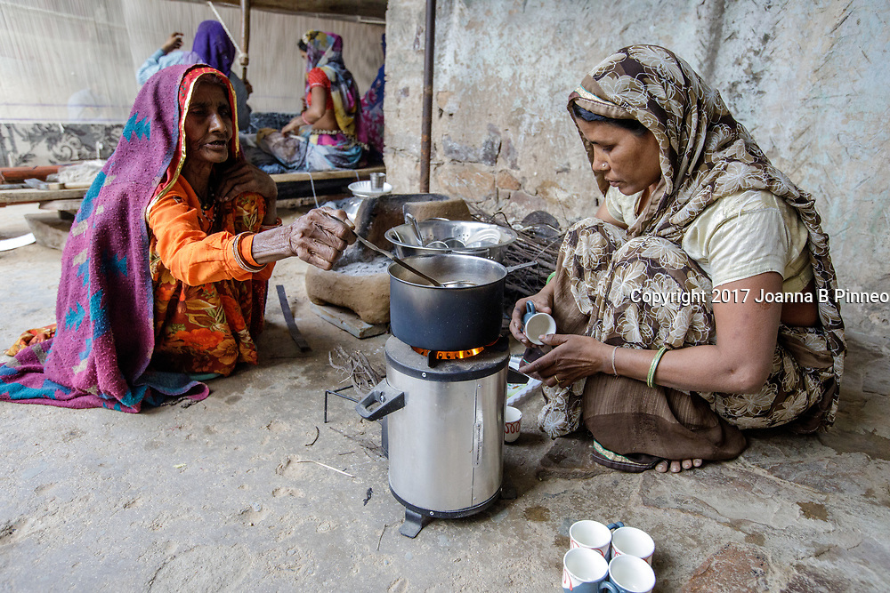 """Shanti Bai makes tea for visitors and her employees using her Greenway Smart Stove to make the tea.  Greenway stoves are made in India. Greenway says that their stoves deliver 60% fuel savings and 70% smoke reduction than the traditional """"chulha"""" or mud stove. Shanti Bai runs a weaving business out of her home with seven looms and twenty-eight women employees. She is part of the Jaipur Rug Foundation weavers. Shanti also uses LPG to cook larger meals and the """"chuhla"""" to cook the chapati or flatbread that is a staple in Indian homes. Often families who have switched to cleaner cooking stoves still practice """"stove stacking"""" which is using more than one type stove at a time, usually the traditional stove and the cleaner one. Some use the traditional stove for specific types of traditional food and some use both at the same time. It can take time for the family cook, usually the woman, to switch completely to the cleaner cooking stove. Shanti Bai says she uses the LPG stove and the Greenway most of the time but still uses the """"chulha"""" for making roti or chapatis."""