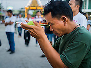 """07 MARCH 2015 - NAKHON CHAI SI, NAKHON PATHOM, THAILAND:  A man prays at the Wat Bang Phra tattoo festival. Wat Bang Phra is the best known """"Sak Yant"""" tattoo temple in Thailand. It's located in Nakhon Pathom province, about 40 miles from Bangkok. The tattoos are given with hollow stainless steel needles and are thought to possess magical powers of protection. The tattoos, which are given by Buddhist monks, are popular with soldiers, policeman and gangsters, people who generally live in harm's way. The tattoo must be activated to remain powerful and the annual Wai Khru Ceremony (tattoo festival) at the temple draws thousands of devotees who come to the temple to activate or renew the tattoos. People go into trance like states and then assume the personality of their tattoo, so people with tiger tattoos assume the personality of a tiger, people with monkey tattoos take on the personality of a monkey and so on. In recent years the tattoo festival has become popular with tourists who make the trip to Nakorn Pathom province to see a side of """"exotic"""" Thailand.  PHOTO BY JACK KURTZ"""