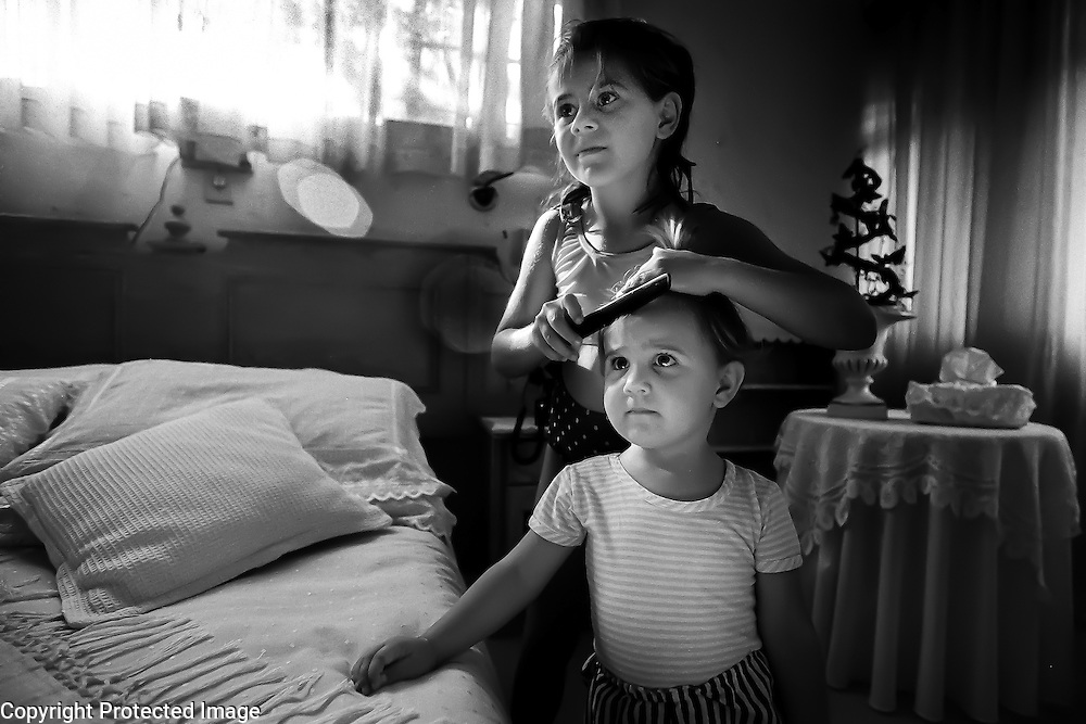 "Ursula Nieuwoudt brushes her sister, Odette's hair after school at the Nieuwoudt's home in the Hennops River area just outside of Johannesburg, South Africa.  Ursula, an Afrikaner (South African of Dutch descent) lives with her parents and two sisters on a farm (not in operation).  Her father, Kobus, is a town planner and consultant and her mother, Annelie, owns a topiary.  The Nieuwoudts employ a live-in cook, domestic servant and several landscapers for Annelie's business.  Their three girls attend a predominantly white school. ""We were brought up very conservatively,"" says Kobus of the changes in South Africa since Apartheid's end.  ""We knew that we had to change.  We never say racist things in front of our children,"" he adds."