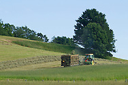 Chester, New York - Taking advantage of beautiful weather on the first day of summer, a farmer in a tractor bales in a field at Brookview Farm on June 21, 2014.