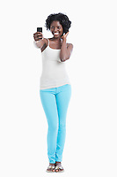 Happy young African American woman taking self portrait over white background