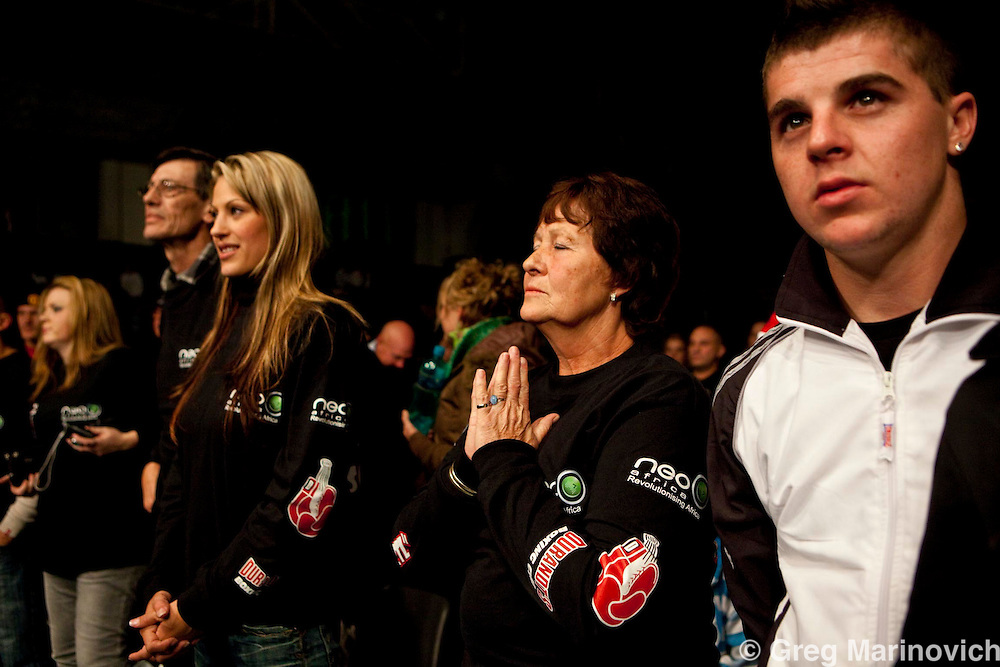 Mikey Schultz wife (centre left, long blonde hair) and his mother (centre right, praying) and other family and friends at  Wembley sports arena, Johannesburg south, Nov 20, 2009, South Africa ahead of the bout. : Self confessed hired killer in the Brett Kebble murder case Mikey Shultz was defeated by Zimbabwean Tineyi Maridzo in the first round of the all WBO Africa title fight in Johannesburg Friday night. The main bout was the world title won by Moruti Baby Face  against Cesar Miranda. Photo Greg Marinovich