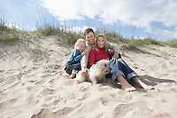 Parents with daughter (5-6) and dog on beach