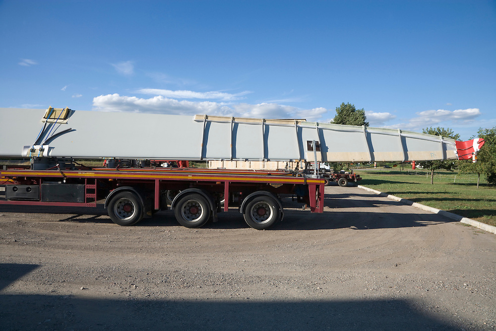 wings of a wind turbine waiting on large flatbeds for transport