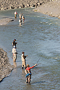 Fishermen catching salmon on Ship Creek in downtown Anchorage, Alaska.