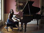 Old Westbury, New York, USA. December 17, 2017. Pianist ANGELINA FUSCO plays Christmas music on Steinway grand piano to entertain visitors at Old Westbury Gardens museum, a former estate of John Shaffer Phipps, during snowy winter holiday weekend on Long Island's Gold Coast.