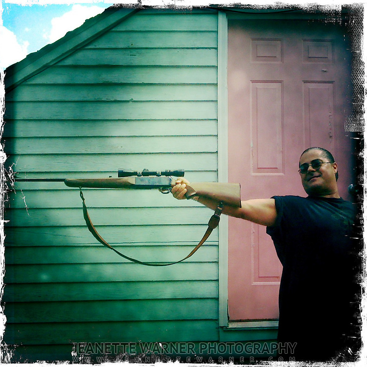 Portrait of a citizen New Orleans showing off his unloaded gun.
