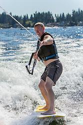 United States, Washington, Lake Sawyer, teen boy surfing behind motorboat.