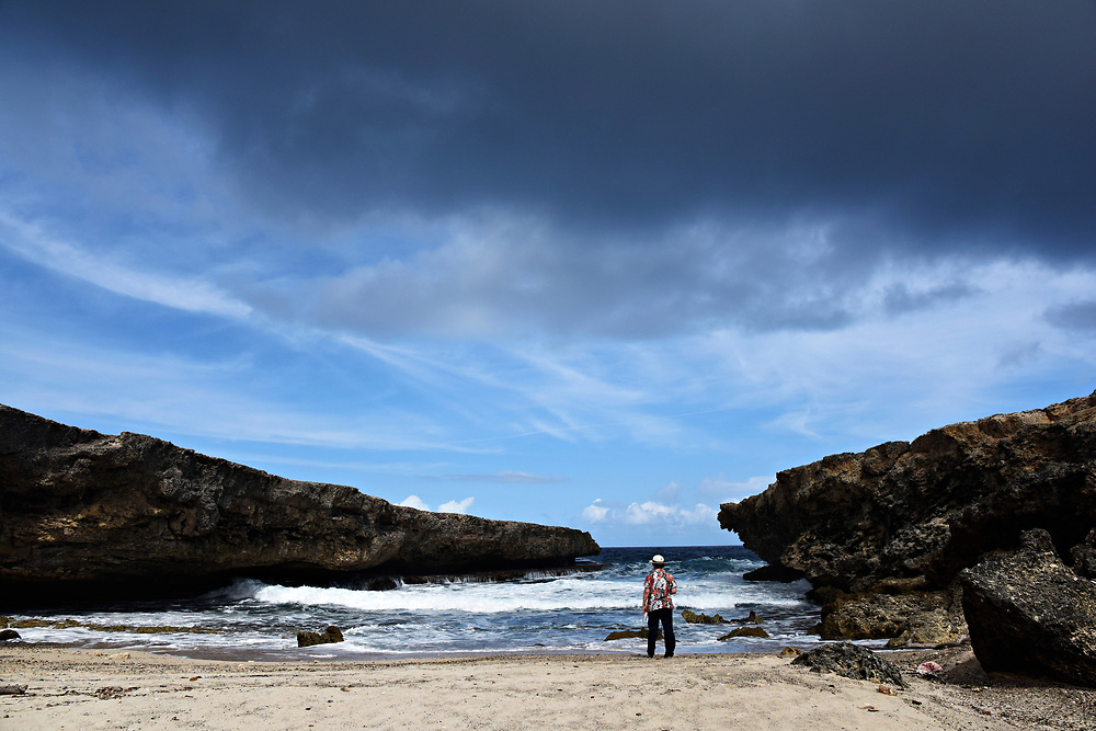 WILLEMSTAD, CURACAO - DECEMBER 12, 2014: A German tourist explores the coastline near the caves at Shete Boka National Park in Curacao's Westpunt region. (photo by Melissa Lyttle)
