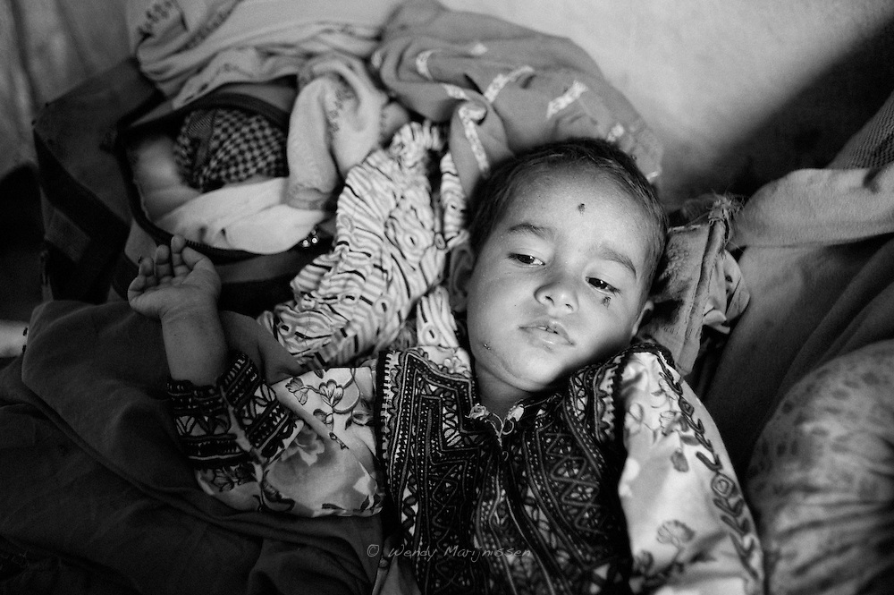 Mehmooda the youngest of Hamida's children getting sleepy. Life for the children is hard in the camp with no sufficient activities and school provided to keep them occupied. Karachi, Pakistan, 2010