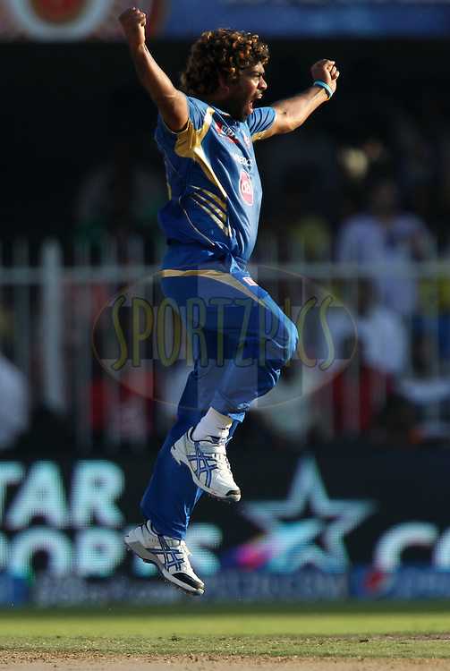 Lasith Malinga of the Mumbai Indians celebrates the wicket of Dinesh Karthik of the Delhi Daredevils during match 16 of the Pepsi Indian Premier League 2014 between the Delhi Daredevils and the Mumbai Indians held at the Sharjah Cricket Stadium, Sharjah, United Arab Emirates on the 27th April 2014<br /> <br /> Photo by Ron Gaunt / IPL / SPORTZPICS