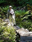 Tom walks a boardwalk on Tuatapere Hump Ridge Track, in Fiordland National Park, South Island, New Zealand. In 1990, UNESCO honored Te Wahipounamu - South West New Zealand as a World Heritage Area.