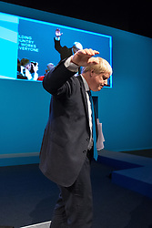 © Licensed to London News Pictures  . 03/10/2017 . Manchester , UK . Foreign Secretary BORIS JOHNSON gives a short wave as he turns to leave the platform after delivering his keynote on day three of the Conservative Party Conference at the Manchester Central Convention Centre . Photo credit : Joel Goodman/LNP