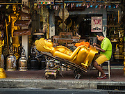 09 MARCH 2016 - BANGKOK, THAILAND: A craftsman engraves the base of a statues of the Buddha on Thanon Bamrung Muang in Bangkok. The street is lined with workshops that make statues of the Buddha and revered Thai Buddhist monks. Once located just outside Bangkok's city walls, it's now in the heart of the city.      PHOTO BY JACK KURTZ