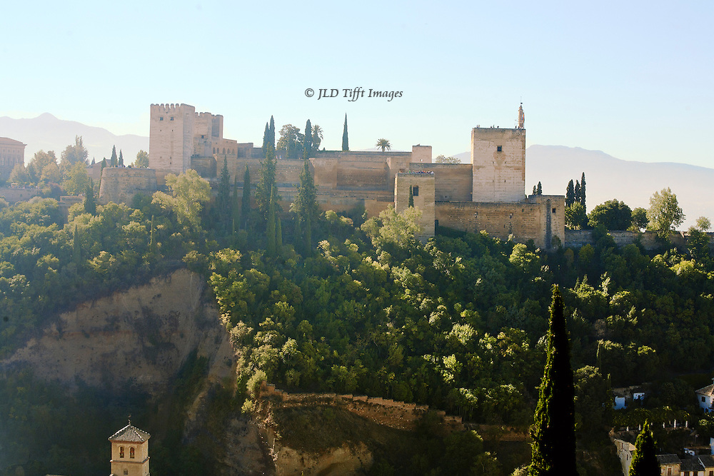 The Alhambra seen from Albaicin in daytime, showing its position on a cliff and squared structure as a fortress. Thick wooded band surrounds it.