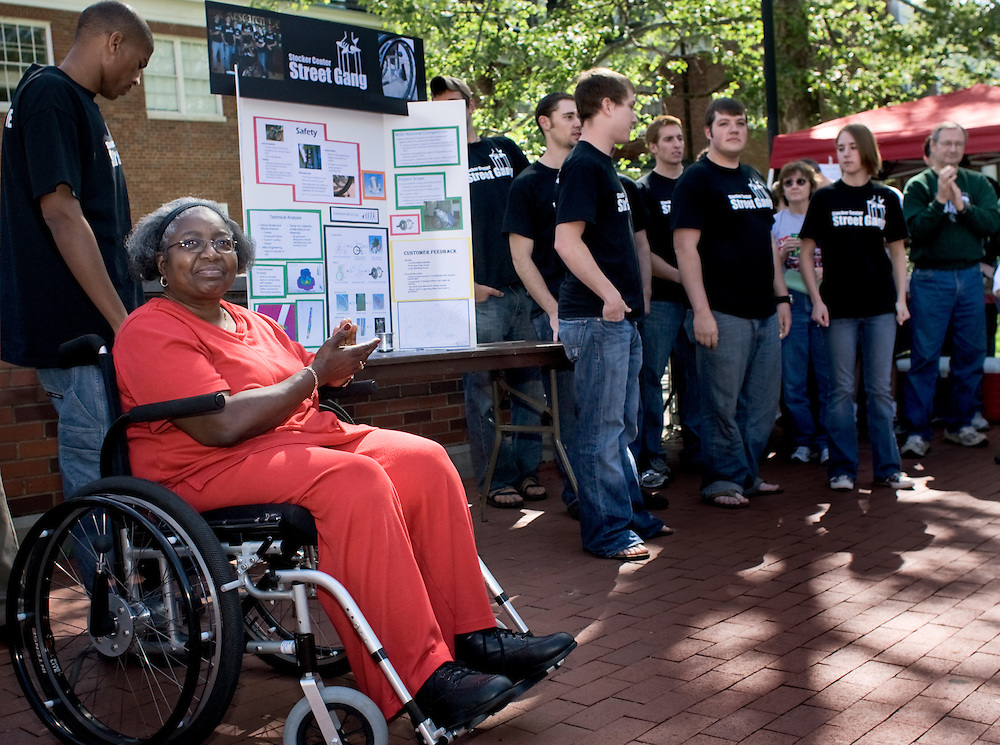 Dr. Carolyn Bailey Lewis, left, applauds the efforts of The Stocker Center Street Gang, the group of OU engineering students that worked on desiging and implementing a self containted geared wheel for use on wheelchairs. The device enables the user to shift gears and more easily ascend an obstacle such as a steep ramp.