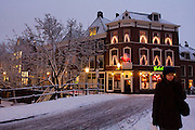 Een vrouw loopt in de schemer bij de Weerdbrug door de sneeuw.<br /> <br /> A woman is walking at twilight in the center of Utrecht.