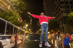 September 21, 2016 - Charlotte, North Carolina, U.S. - Sept. 21, 2016 - A protestor stands on the hood of a car during a protest and eventual riot in uptown. This is the second day of violence that erupted after a police officer's fatal shooting of an African-American man Tuesday afternoon. (Credit Image: © Sean Meyers via ZUMA Wire)