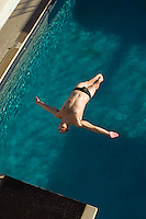 Male swimmer diving into swimming pool